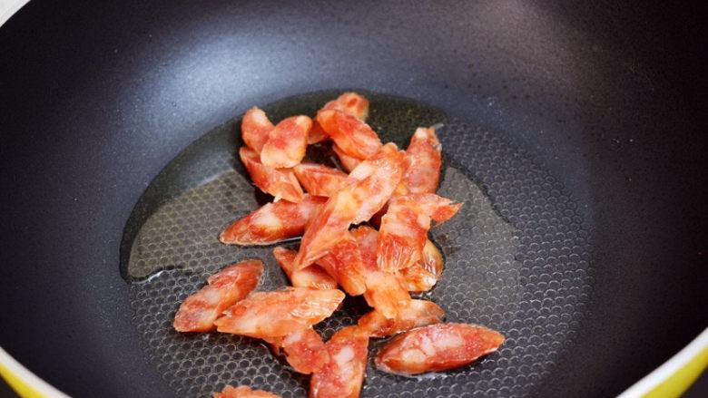 青椒炒香肠,锅中倒入适量的食用油烧热,放入腊肠翻炒至变色