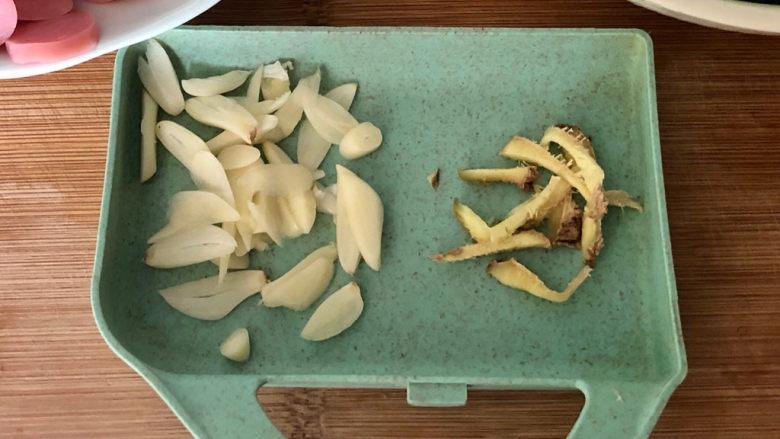 青椒炒香肠,开始改刀:蒜切蒜片,姜切姜丝