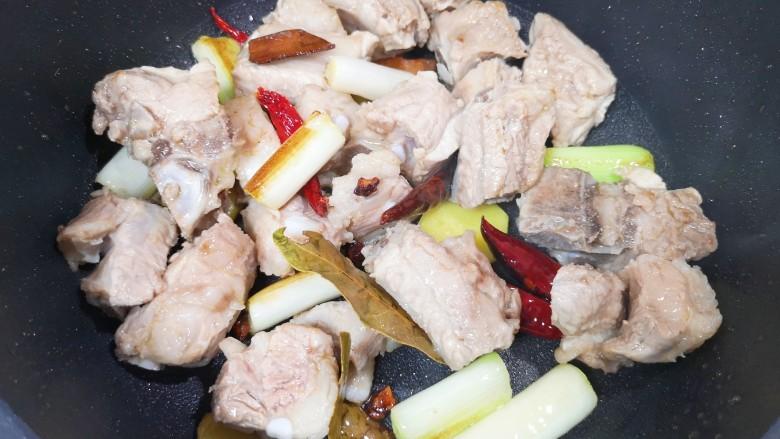 土豆排骨焖饭,下入排骨,翻炒至排骨表面微微发黄。