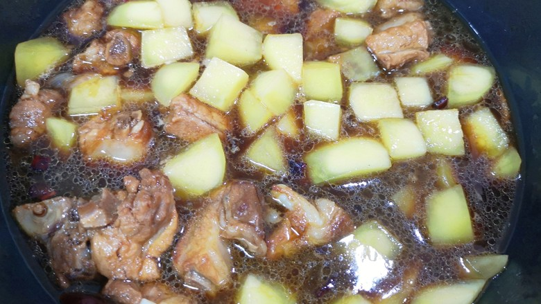 土豆排骨焖饭,40分钟以后,给排骨里面下入土豆翻炒均匀,炖5分钟。