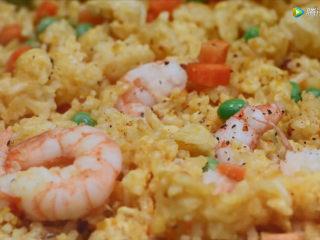 耳光炒饭,4、将包裹了蛋液的隔夜米饭翻炒均匀至上色,依次放入咸蛋黄、胡萝卜丁、虾仁等,再加入一勺盐调味,出锅。