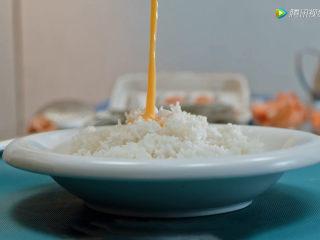 耳光炒饭,2、将鸡蛋打散,蛋液倒入隔夜米饭中均匀搅拌。