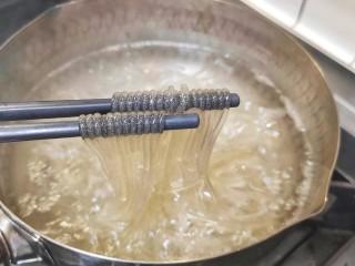 豆芽炒粉条,锅中加入适量清水,加入红薯粉,煮几分钟,红薯粉熟了就马上夹出来,不要煮的时间太长,以免红薯粉变得太软,容易断,影响整体口感。