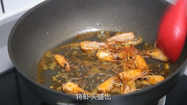 耳光炒饭,锅里烧热油,放虾头翻炒出红油后捞出
