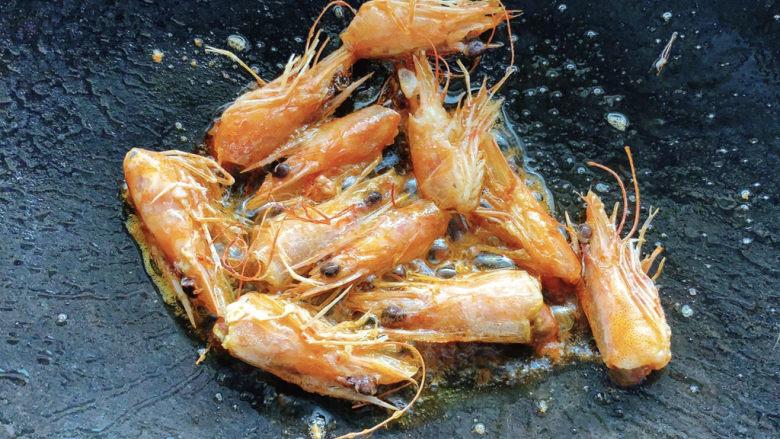 耳光炒饭,热油锅加少许油,将虾头放入。