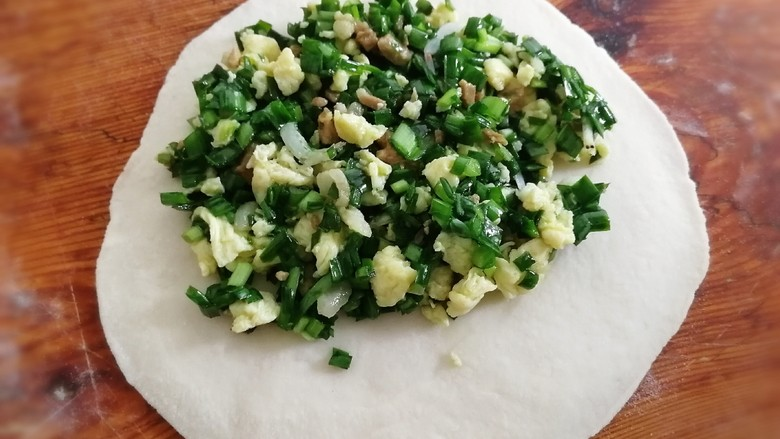 韭菜盒子,取一个面剂,滚圆、按扁,擀成中间微厚四周薄的圆形,放入拌好的馅料。