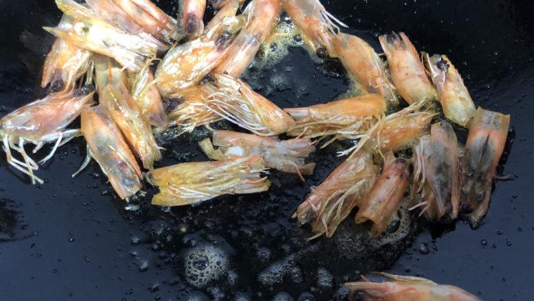 耳光炒饭,热锅冷油下虾头,小火煸炒出油后,挑出虾头丢弃。