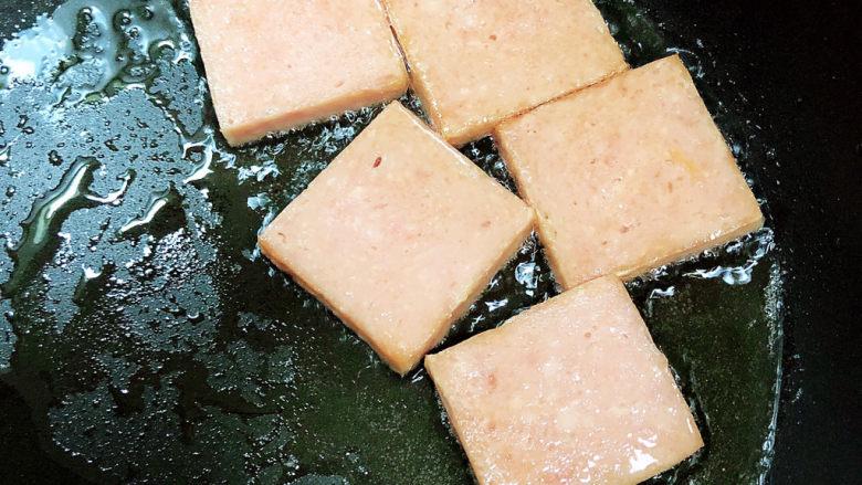 耳光炒饭,锅中倒入油,加热至五成热,放入午餐肉片,煎至两面金黄即可,捞出待用。