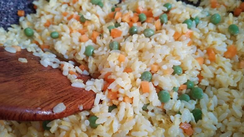 耳光炒饭,倒入胡萝卜、豌豆,再炒半分钟
