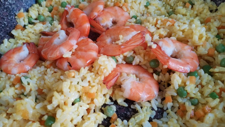 耳光炒饭,最后倒入大虾,放入一点盐,翻炒均匀。口味重的可以再加一点十三香出味