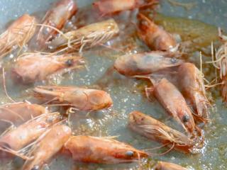 耳光炒饭,起锅热油,油热后放入虾头,炒出红色的虾油