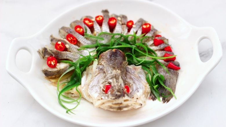 清蒸鲈鱼,把蒸鱼后的汤汁倒掉不用,先摆上小米辣,再撒上葱丝。