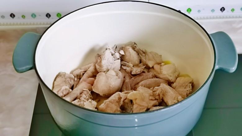新疆大盘鸡,锅中加入食用油,加入蒜煸炒,再倒入鸡块翻炒。