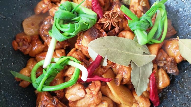 新疆大盘鸡,放小葱结、八角、香叶和干红辣椒炒香(如果能吃辣可以将干红辣椒掰开)。