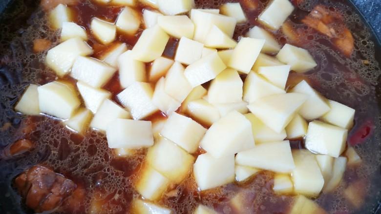 新疆大盘鸡,25分钟以后鸡块已经熟了,下入土豆翻炒均匀,炖5分钟左右。
