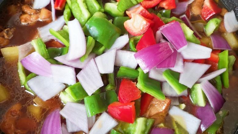 新疆大盘鸡,下入红彩椒、青椒和洋葱翻炒1-2分钟即可关火。