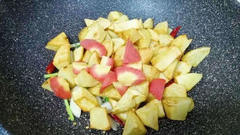 红烧土豆,下入红萝卜和煎好的土豆翻炒均匀。