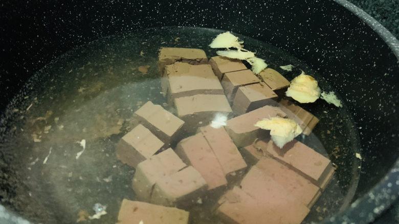 鸭血炒菠菜,锅加清水,加姜片,煮开,加入鸭血