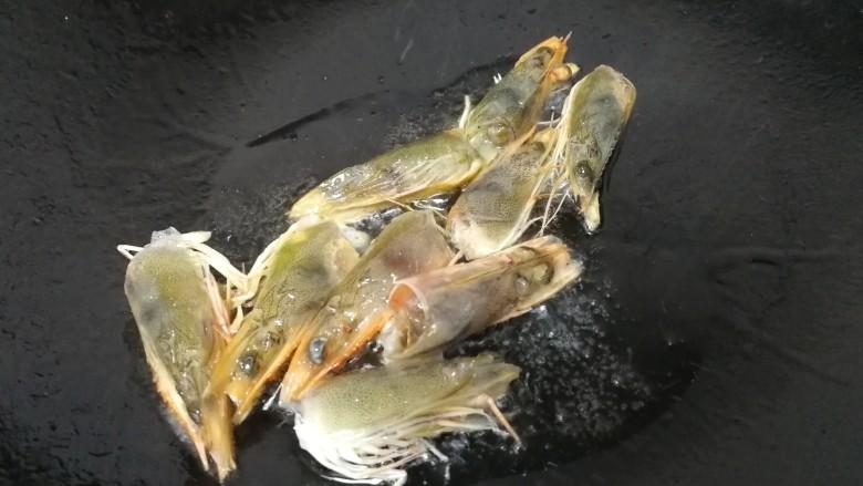 西芹炒虾仁,热锅凉油,油微热放入虾头。