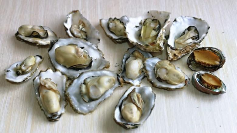 蒜蓉生蚝,依次掰开并处理好了内脏,用手拿着贝壳,一个一个的冲洗干净。