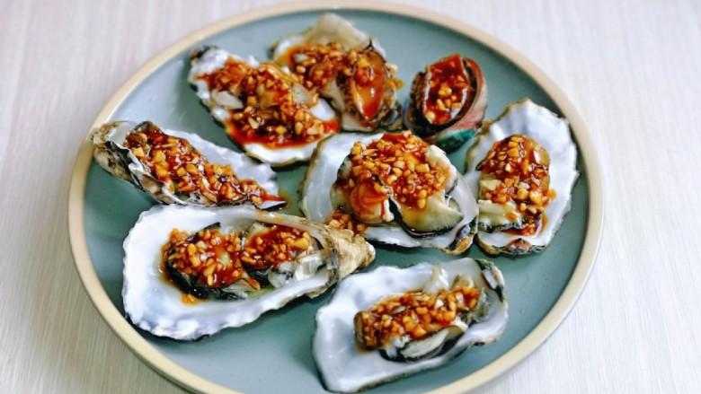 蒜蓉生蚝,用小勺每个贝壳里面盛一勺酱汁,也可以根据个人喜好选择。