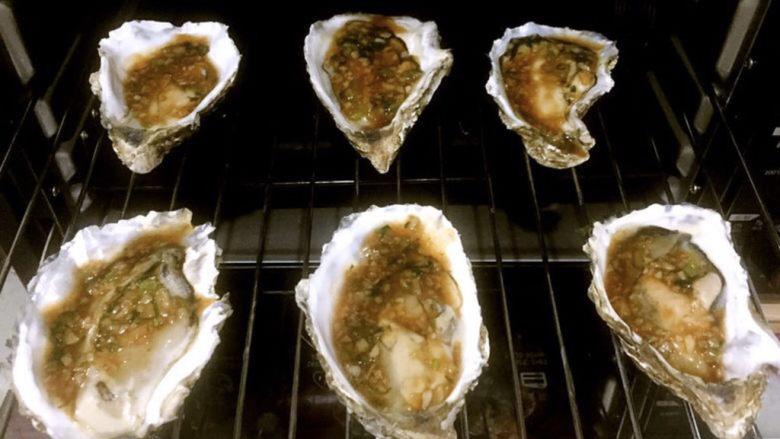蒜蓉生蚝,牡蛎依次淋上料汁再放入烤箱中烤五分钟