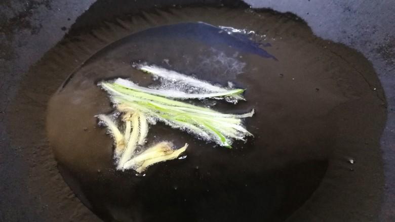 西芹炒牛肉,热锅凉油,放入葱姜丝,文火炒香。