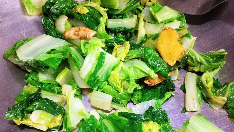 白菜豆腐汤,锅留底油,下入姜片煸炒出香味,下入小白菜翻炒均匀