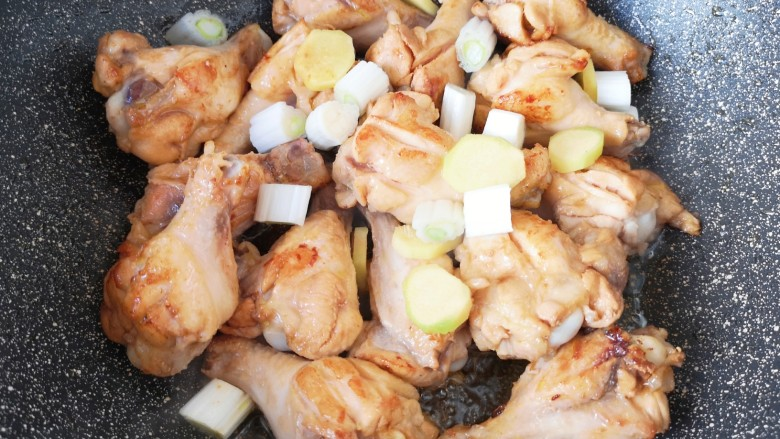可乐鸡翅根,下入葱段和姜片。