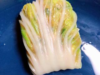 白菜包肉,从一头卷起,包裹起来。
