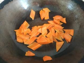 青椒炒胡萝卜,锅中放入适量植物油,放入胡萝卜翻炒至变软,盛出待用