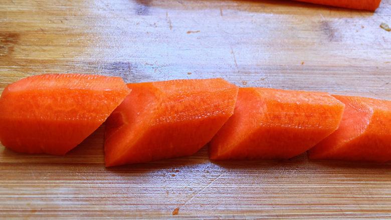 青椒炒胡萝卜,这里有一个切菱形片的小窍门,用这个方法很简单就能切除漂亮的菱形片。对半切开的胡萝卜,斜切一刀,去掉胡萝卜根部的部位,使其呈斜面状,然后,间隔一寸长度,再斜切,以此类推