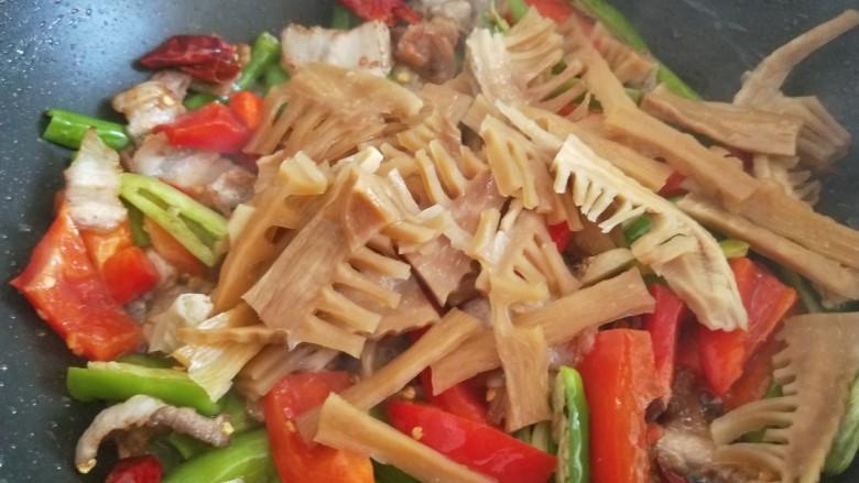 尖椒土豆片,倒入笋干炒均匀。