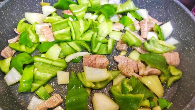 尖椒土豆片,加入洋葱和尖椒,炒两分钟
