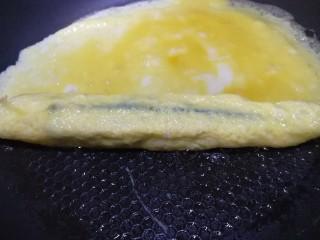 秋葵厚蛋烧,用刚刚凝固的蛋皮卷起秋葵,中小火边卷边煎,全都卷起。