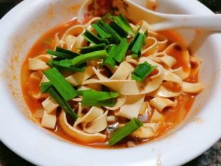 水煮千张,煮两分钟后再把千张连汤一起倒入配菜上面,再撒点蒜苗