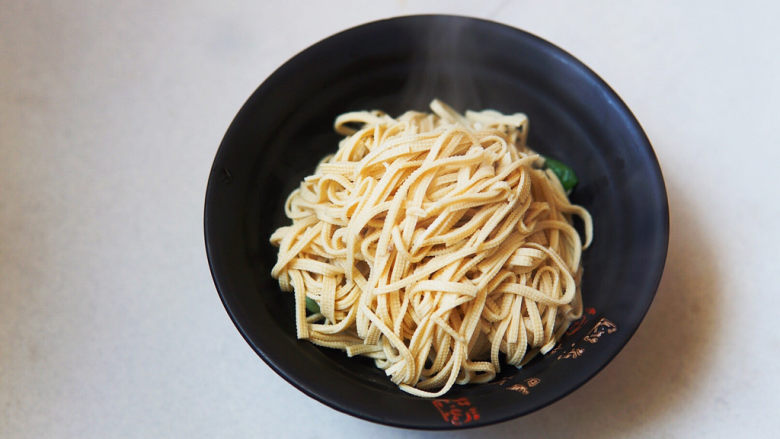 水煮千张,煮好的豆皮丝放在小油菜上,加入煮豆皮的汤
