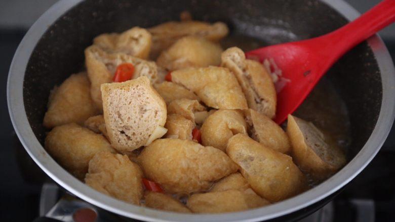 红烧油豆腐,煮至豆腐充分的吸饱汤汁后大火翻炒收汁