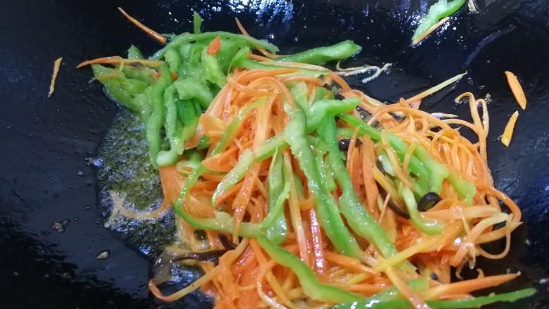 鱼香肉丝,锅里底油先放入胡萝卜丝煸炒均匀,再放尖椒丝文火炒匀。