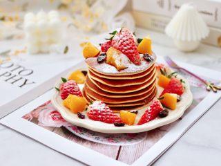 酸奶水果松饼,烙好的松饼摞到盘中,放入草莓和黄桃,黑葡萄干,撒上糖粉装饰即可享用。