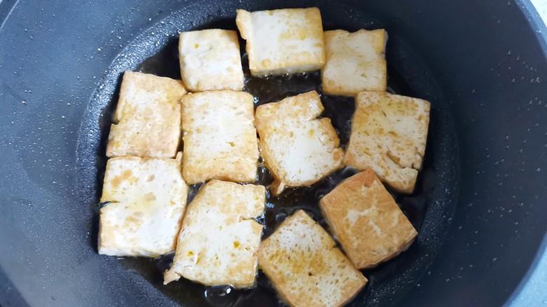 白菜炒豆腐,热锅入油,放入豆腐煎至两面金黄盛出。