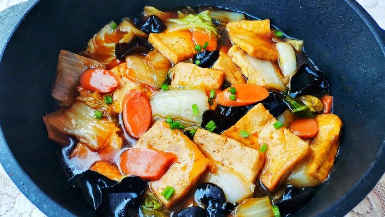 白菜炒豆腐,盖上锅盖大火煮开转小火煮至汤汁浓稠,撒葱花。