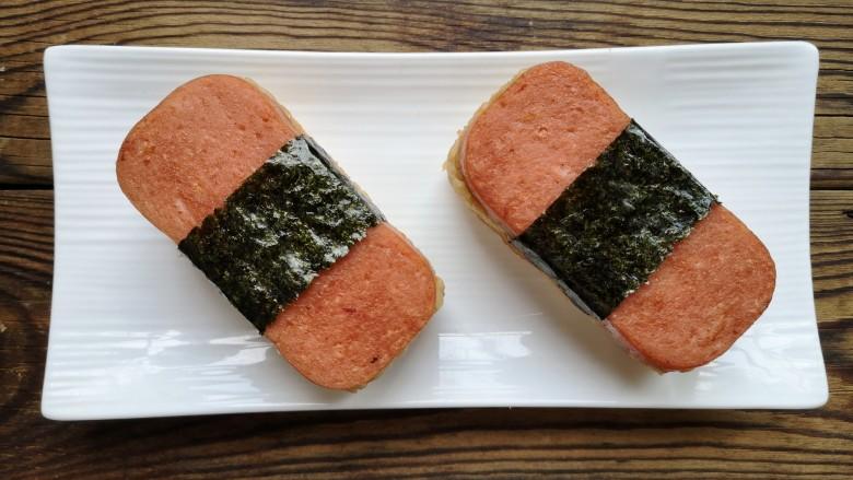 午餐肉饭团,轻轻把袋子提出来,再包上一片<a style='color:red;display:inline-block;' href='/shicai/ 279'>海苔</a>。