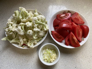 开胃番茄花菜,花菜洗净切小朵,番茄和葱蒜切好