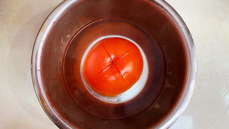 西红柿炒豆腐,<a style='color:red;display:inline-block;' href='/shicai/ 3551'>西红柿</a>划十字,开水浸泡去皮。