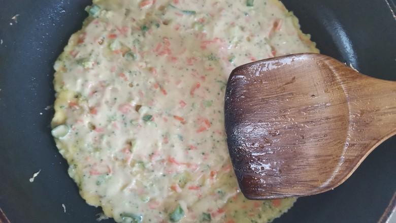 胡萝卜鸡蛋饼,用铲子把面糊摊均匀摊成饼状