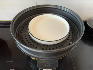 经典小吃驴打滚,放入锅中,盖上保鲜膜,戳洞上锅蒸二十分钟
