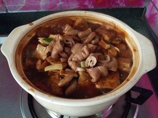 肥肠炖豆腐,和肥肠及葱姜蒜,一起倒入砂锅中,开盖,大火煮沸