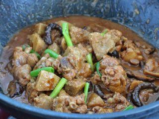 香菇炖鸡腿,最后调入适量的盐,改大火翻炒收汁,出锅前撒入葱叶段即可。