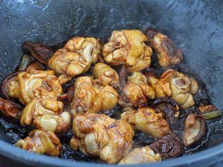香菇炖鸡腿,调入生抽、老抽和料酒翻炒上色,再将香菇块放进去翻炒均匀。